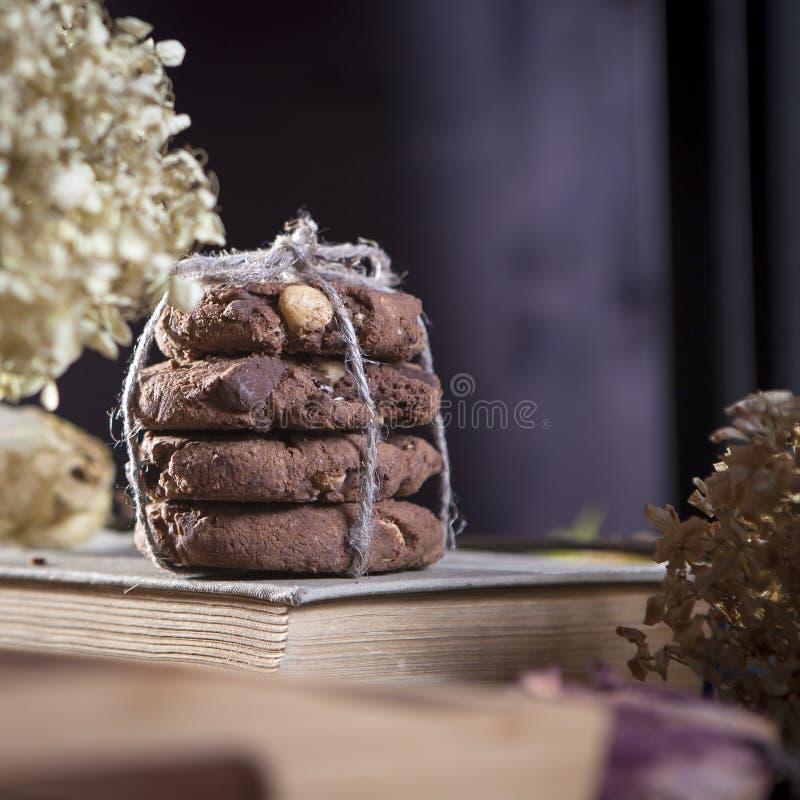 Os biscoitos escuros do chocolate com as porcas no fundo de madeira escuro imagens de stock