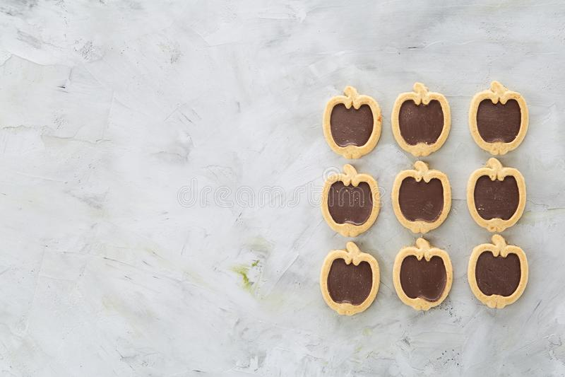 Os biscoitos pomiformes arranjados nas fileiras na luz textured o fundo, close-up, profundidade de campo rasa, foco seletivo fotografia de stock