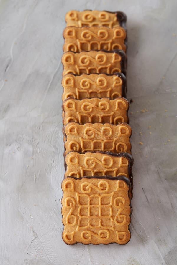 Os biscoitos quadrados arranjados no teste padrão na luz textured o fundo, close-up, profundidade de campo rasa, foco seletivo fotos de stock royalty free