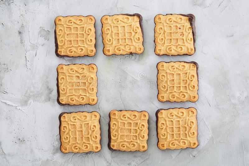 Os biscoitos quadrados arranjados no teste padrão na luz textured o fundo, close-up, profundidade de campo rasa, foco seletivo foto de stock royalty free