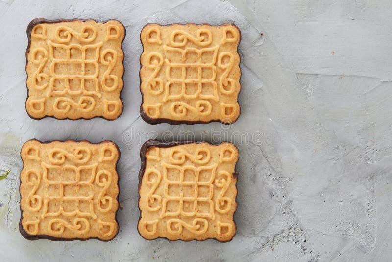 Os biscoitos quadrados arranjados no teste padrão na luz textured o fundo, close-up, profundidade de campo rasa, foco seletivo imagens de stock