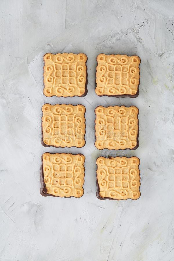 Os biscoitos quadrados arranjados no teste padrão na luz textured o fundo, close-up, profundidade de campo rasa, foco seletivo foto de stock