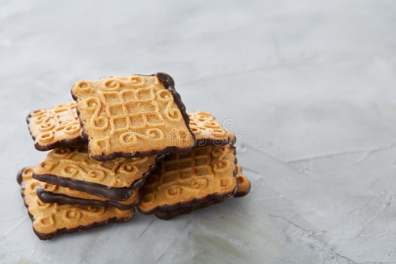 Os biscoitos quadrados arranjados no teste padrão na luz textured o fundo, close-up, profundidade de campo rasa, foco seletivo fotografia de stock royalty free