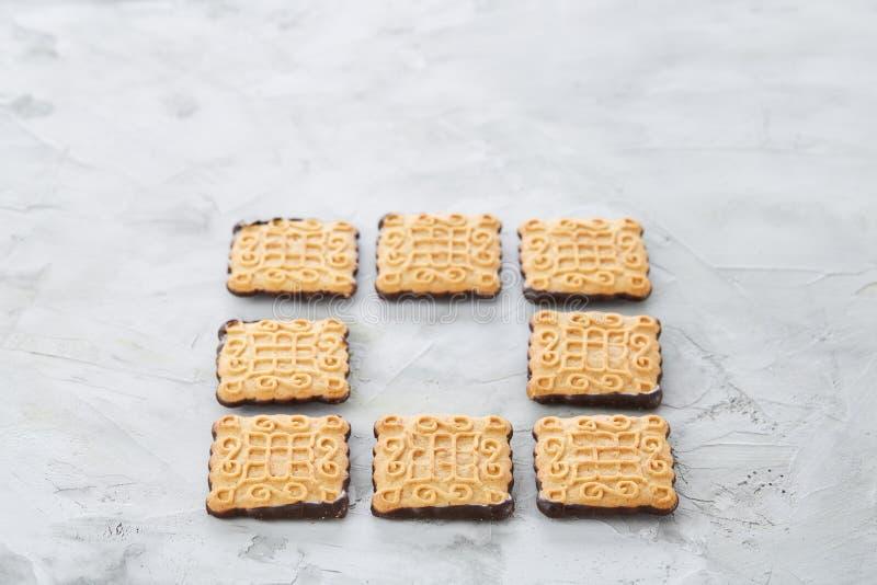 Os biscoitos quadrados arranjados no teste padrão na luz textured o fundo, close-up, profundidade de campo rasa, foco seletivo imagem de stock royalty free
