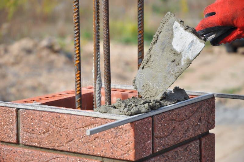 Os blocos do clinquer de Worker Installing Red do pedreiro e a alvenaria do tijolo da calafetagem articulam a parede exterior com imagens de stock