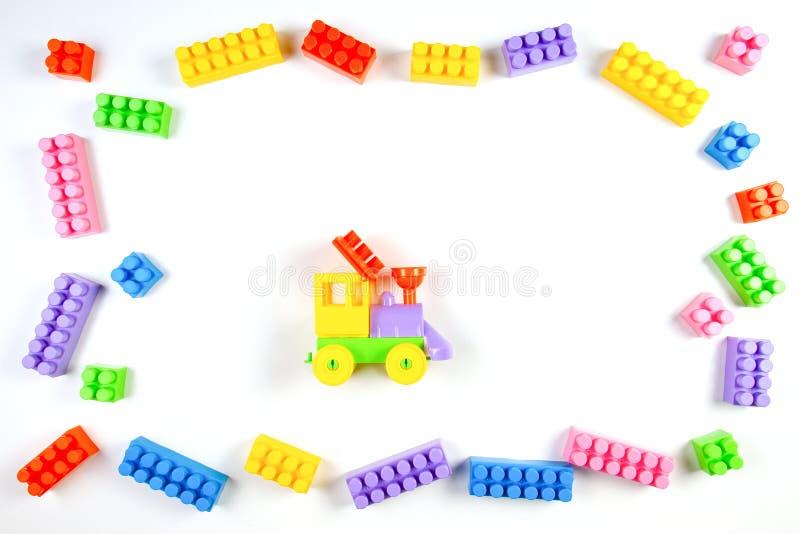 Os blocos e o brinquedo plásticos coloridos da construção treinam no fundo branco enquanto as crianças brincam o quadro imagem de stock