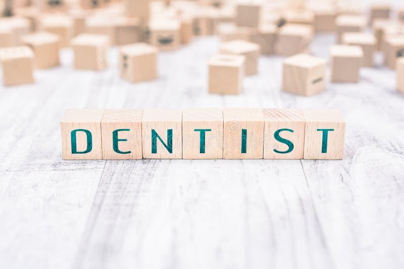 Os blocos em uma tabela branca, conceito de Formed By Wooden do dentista da palavra do lembrete fotografia de stock