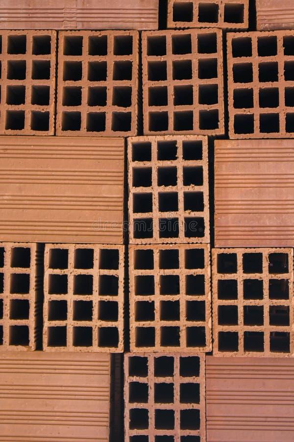Os blocos ocos vermelhos arranjaram haphazardly em uma pilha Textura ou fundo interessante da constru??o com espa?o da c?pia fotografia de stock royalty free