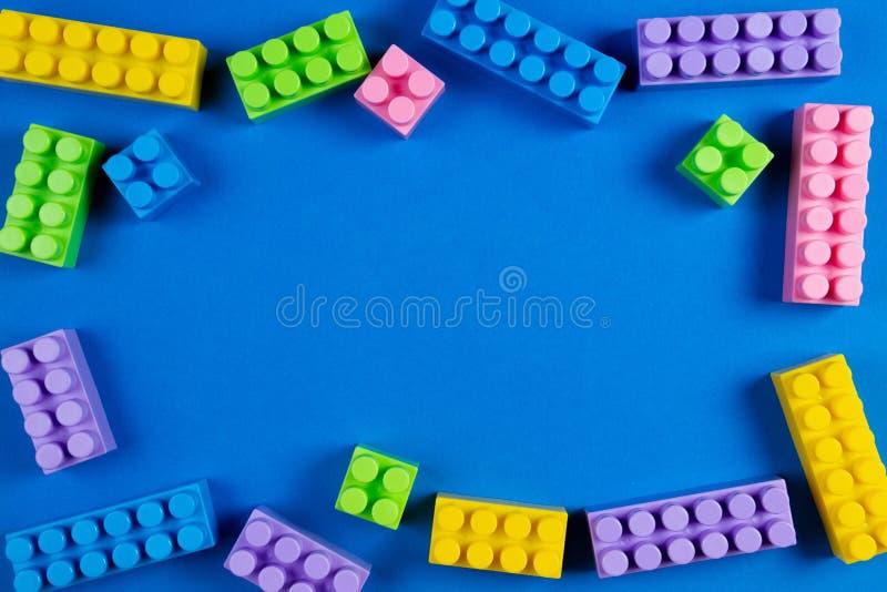 Os blocos plásticos coloridos da construção no fundo azul como crianças brincam o quadro foto de stock royalty free