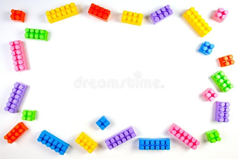 Os blocos plásticos coloridos da construção no fundo branco como crianças brincam o quadro fotografia de stock royalty free