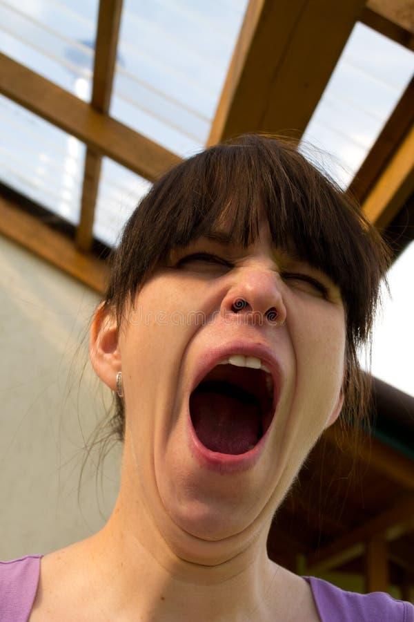 Os bocejos da mulher extensamente que abrem uma boca foto de stock