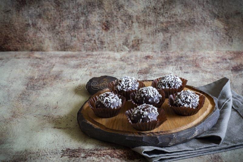 Os bolos de chocolate deliciosos polvilham o coco em uma placa de madeira bonita com um guardanapo cinzento imagens de stock