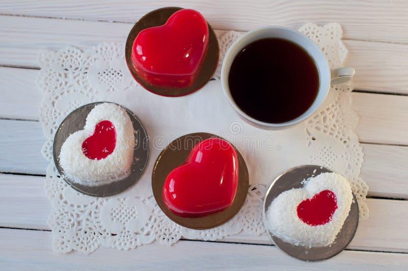 Os bolos vermelhos e brancos na forma do coração colocam na tabela de madeira perto do copo do chá Vista superior fotos de stock
