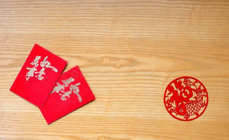 Os bolsos e o papel vermelhos chineses de Traidtional cortaram na tabela imagem de stock royalty free