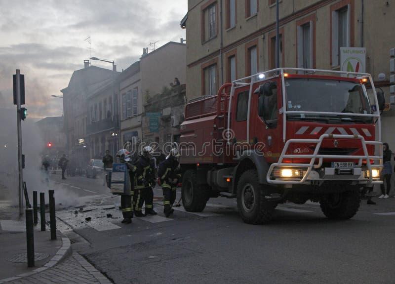 Os bombeiros estão pondo para fora o fogo durante a demonstração de vestes amarelas imagens de stock