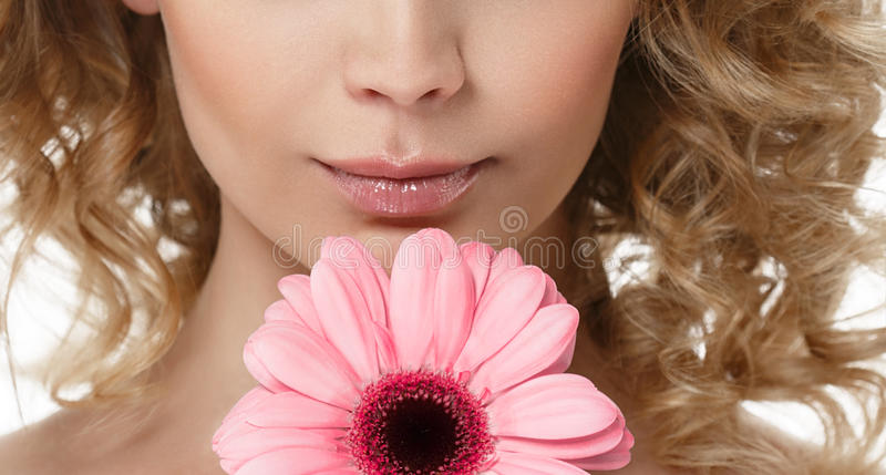 Os bordos da mulher cheiram o retrato da beleza do queixo com a flor no cabelo louro encaracolado do cabelo fotos de stock royalty free