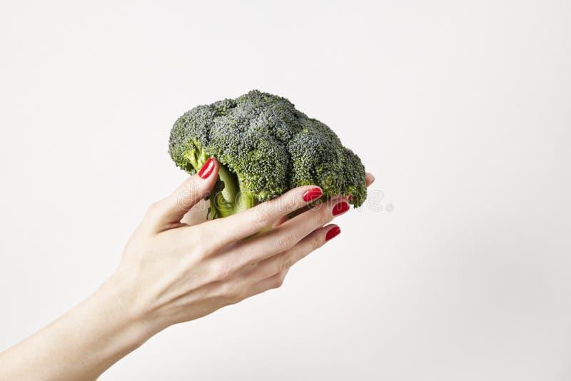 Os brócolis do legume fresco na mão estendido da mulher, dedos com vermelho pregam o tratamento de mãos, isolado no fundo branco, imagens de stock royalty free