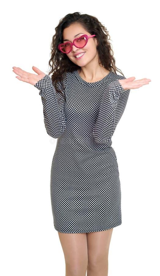 Os braços abertos da moça, retrato da beleza, vestido quadriculado preto e branco, óculos de sol cor-de-rosa no coração dão forma foto de stock royalty free
