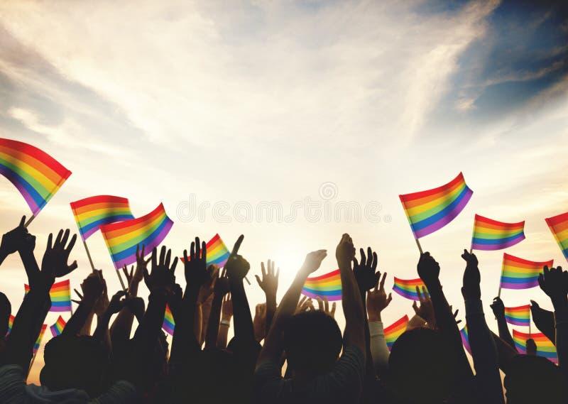 Os braços alegres da celebração da multidão da bandeira do arco-íris levantaram o conceito fotografia de stock royalty free