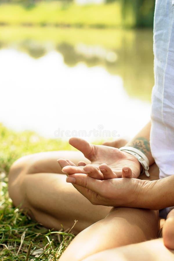 Os braços cruzados são postos sobre os pés da menina na meditação fotografia de stock royalty free