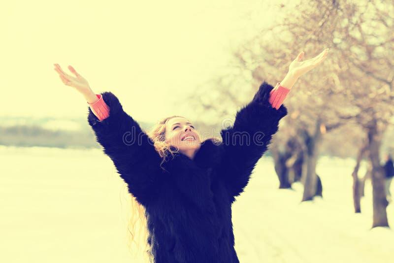 Os braços de sorriso da mulher aumentaram até o céu, comemorando a liberdade fora imagem de stock