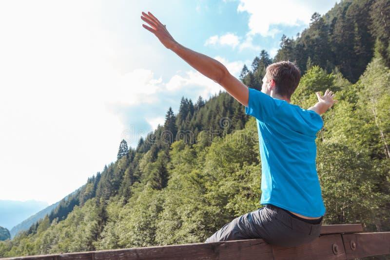 Os braços do homem aumentaram em uma ponte que cruza um rio cercado por montanhas fotografia de stock