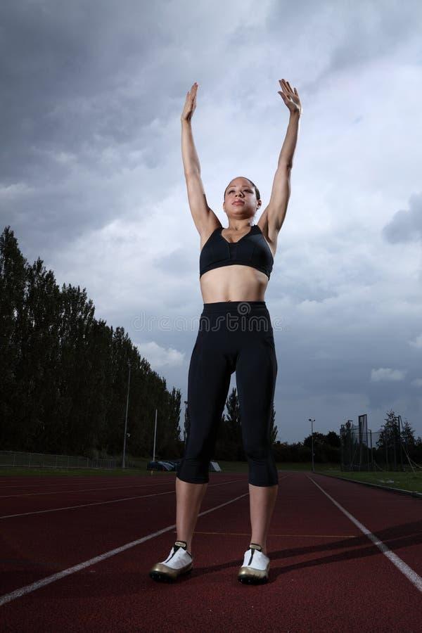 Os braços do sucesso levantaram para o atleta fêmea na trilha foto de stock