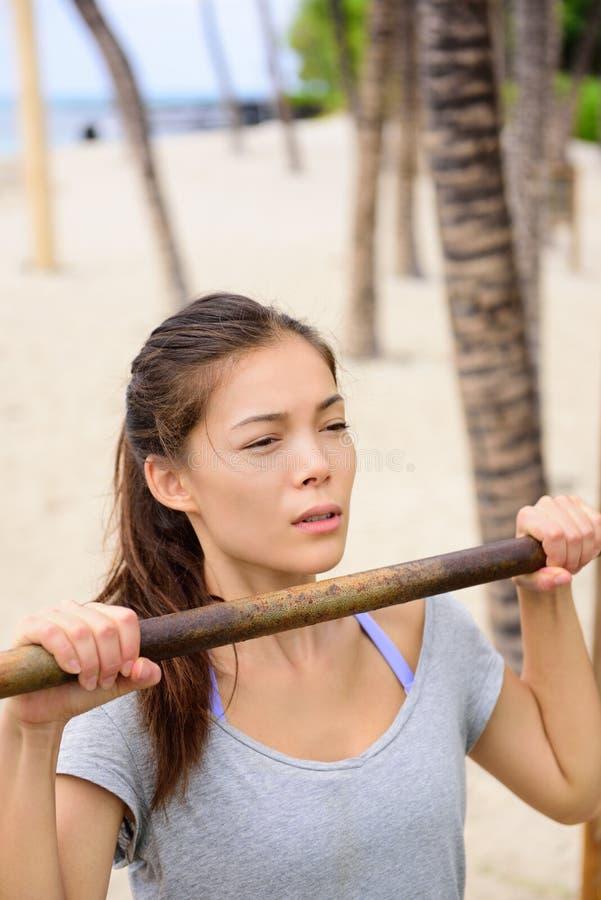 Os braços do treinamento da mulher do exercício levantam sobre a barra fotografia de stock