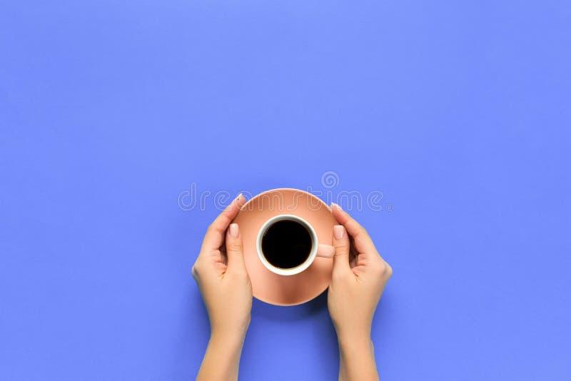 Os braços fêmeas guardam a caneca de café no fundo roxo vista superior com para lidar espaço imagem de stock