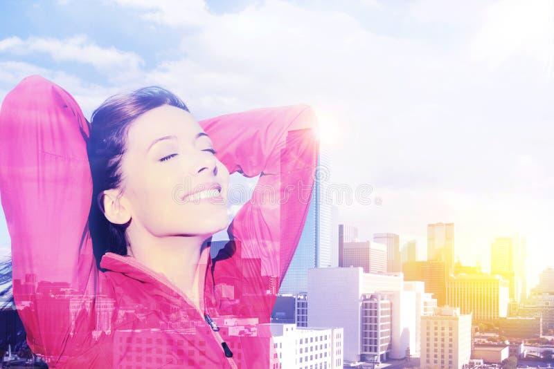 Os braços felizes da mulher da cidade aumentaram na alegria que toma a respiração profunda que comemora a liberdade foto de stock royalty free