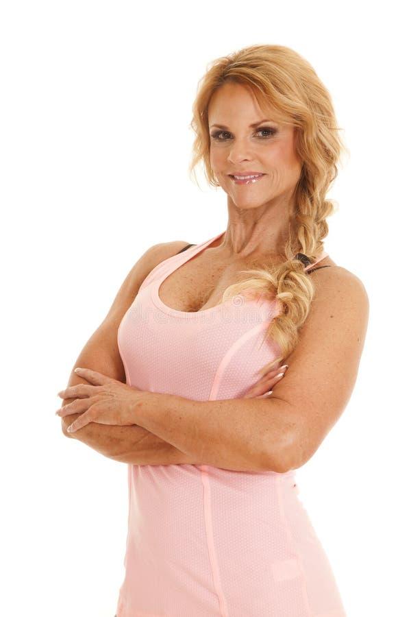 Os braços maduros do tanque do rosa da mulher dobraram o sorriso lateral fotos de stock