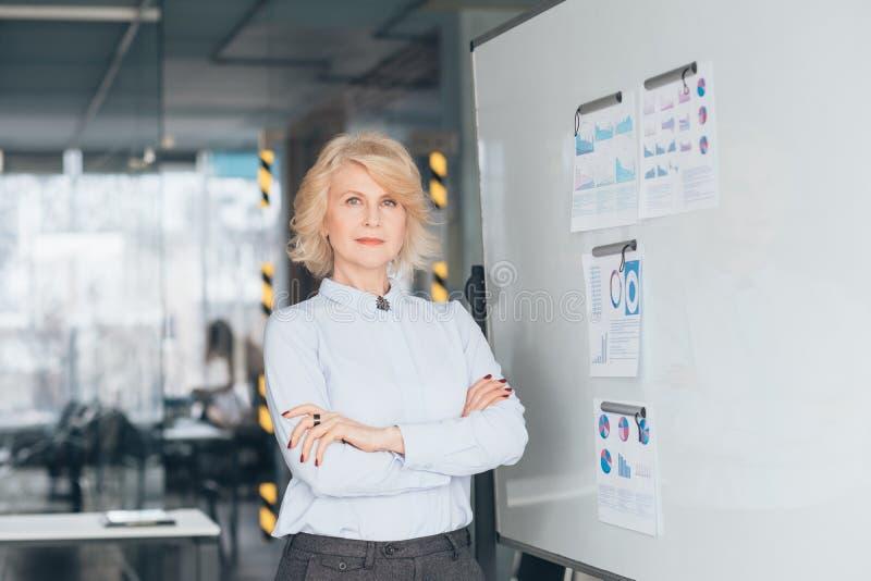 Os braços seguros da mulher de negócio dobraram o treinador superior foto de stock royalty free
