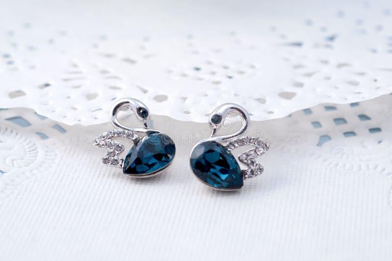 Os brincos da safira gostam de pares de A de cisnes azuis foto de stock royalty free