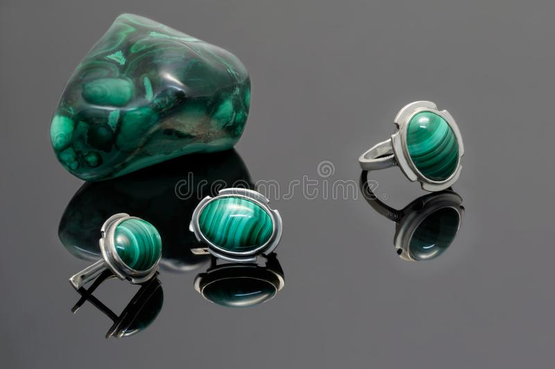 Os brincos e o anel de prata do close up com malaquite no fundo da malaquite apedrejam a parte na mesa acrílica preta imagens de stock