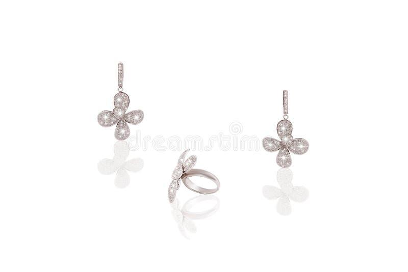 Os brincos preciosos da platina soam a fêmea da flor com os diamantes no fundo isolado branco imagens de stock royalty free