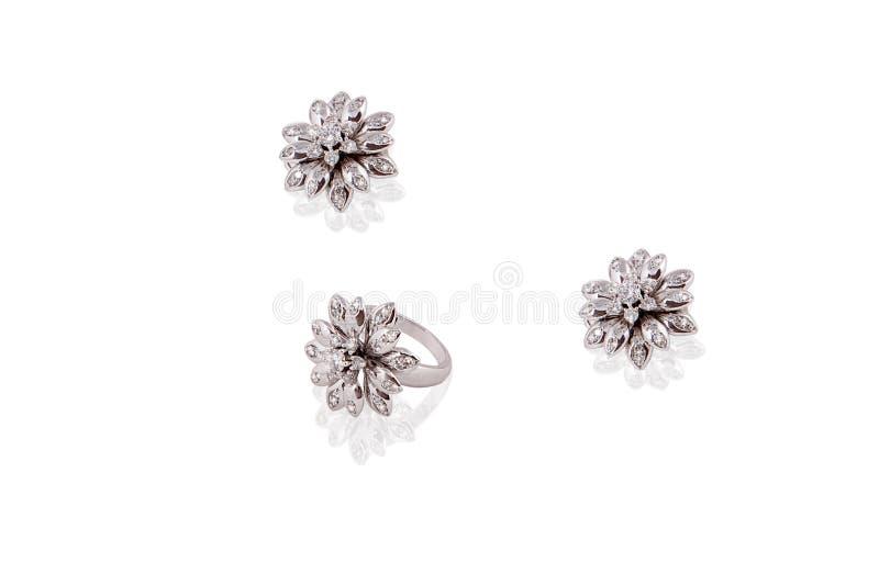 Os brincos preciosos da platina soam a fêmea da flor com os diamantes no fundo isolado branco fotografia de stock