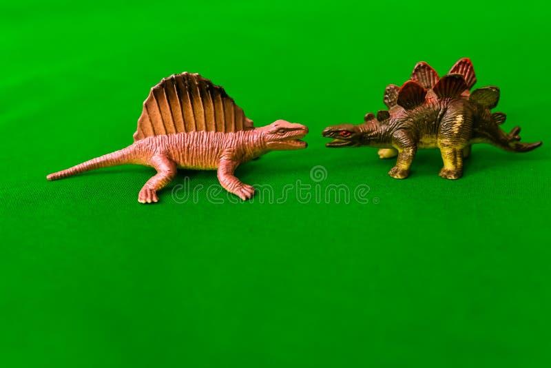 Os brinquedo-dinossauros das crianças, em um verde ou em um fundo cinzento imagens de stock royalty free