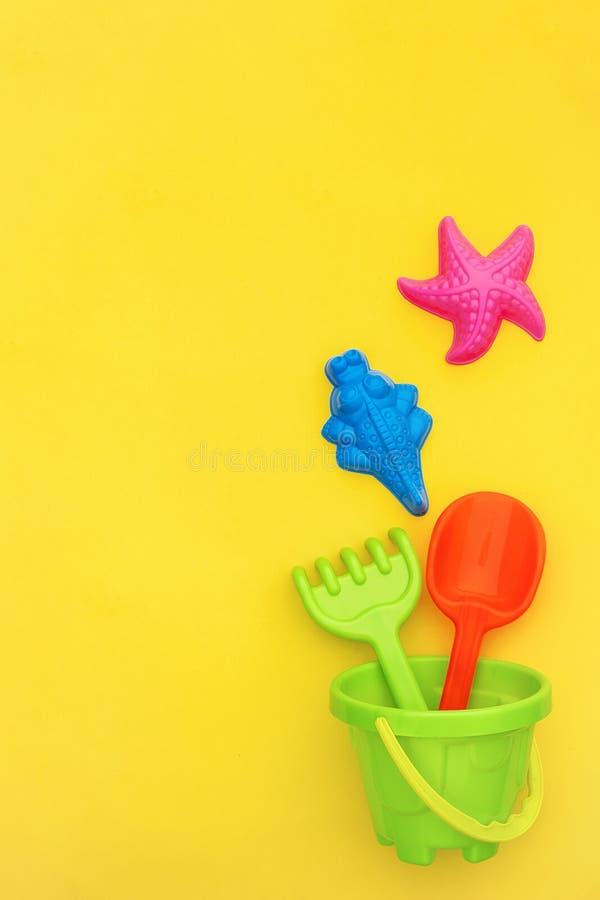 Os brinquedos coloridos das crianças do grupo para jogos do verão na caixa de areia ou no Sandy Beach no fundo amarelo com espaço fotografia de stock royalty free
