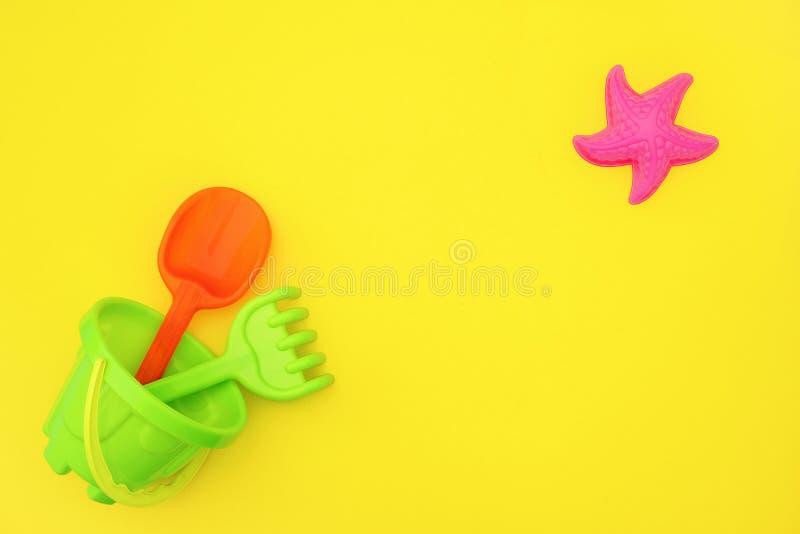 Os brinquedos coloridos das crianças do grupo para jogos do verão na caixa de areia ou no Sandy Beach no fundo amarelo com espaço imagem de stock
