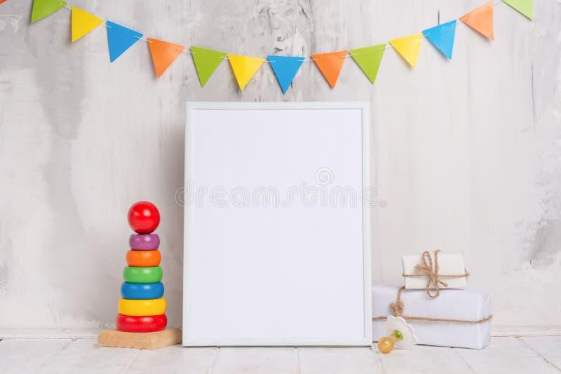 Os brinquedos das crianças, com um quadro branco o quadro em um fundo claro da parede com sinais das crianças, para o projeto, di fotos de stock royalty free