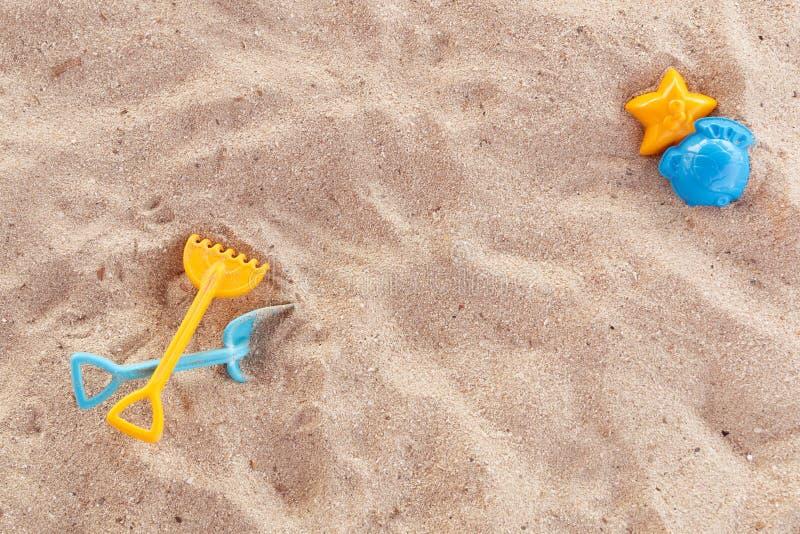 Os brinquedos das crianças plásticas brilhantes na areia Conceito da recreação da praia para crianças Jogos do verão do ` s das c imagens de stock royalty free