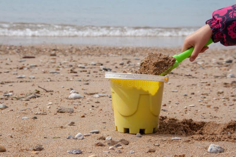 Os brinquedos das crian?as pl?sticas brilhantes na areia Conceito da recrea??o da praia para crian?as fotos de stock