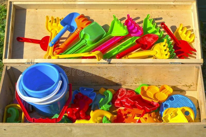 Os brinquedos do ` s das crianças para caixas de areia são empilhados em uma caixa de madeira fotografia de stock