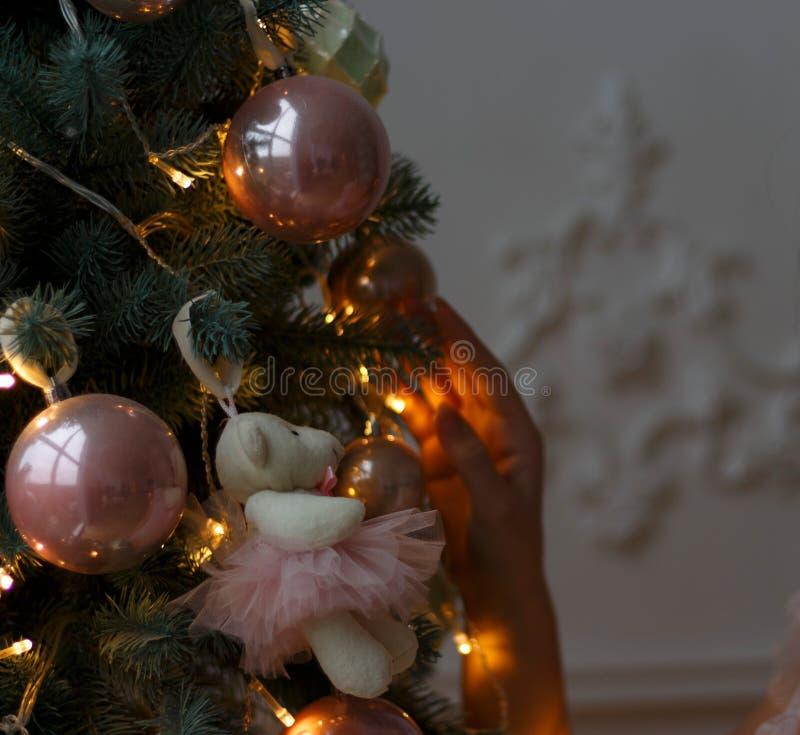 os brinquedos e um urso cor-de-rosa estão pendurando na árvore decore a árvore, preparar-se para o feriado Manhã de Natal imagens de stock royalty free