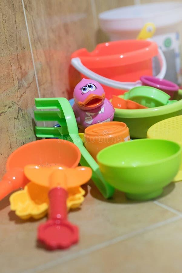 Os brinquedos plásticos do banho das crianças põem no banheiro que têm um pato pequeno cor-de-rosa no meio imagem de stock royalty free