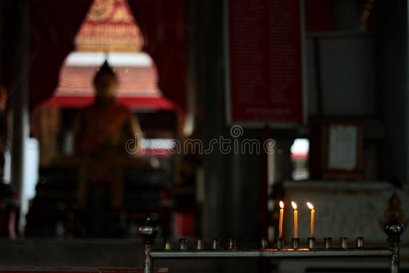 Os budistas fazem o mérito, colocando uma vela iluminada e iluminaram o incenso com quadro das velas no altar da Buda no templo s fotos de stock