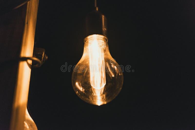 Os bulbos incandescentes retros amarelos penduram na noite em um partido Ampolas que penduram em uma ponte de madeira na noite imagem de stock royalty free