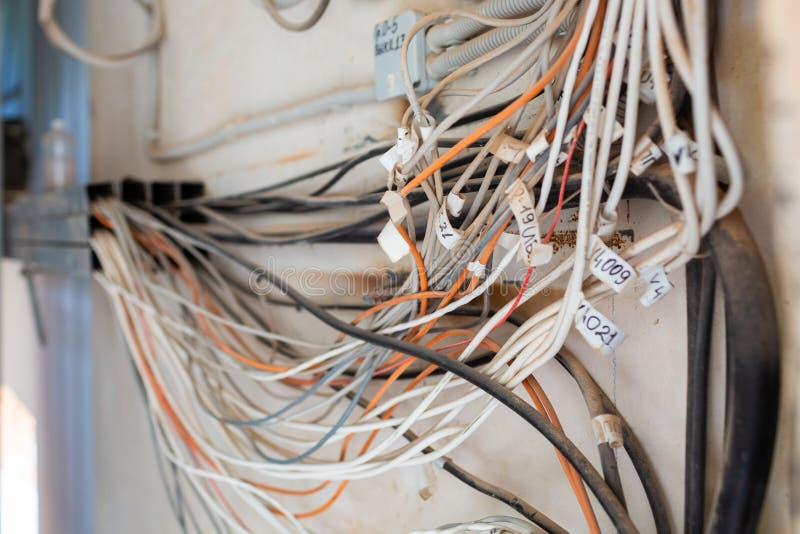 Os cabos de muito UTP do Internet, dos ethernet e os cabos elétricos com etiquetas sem bandejas de cabo são provisórios instalada fotografia de stock
