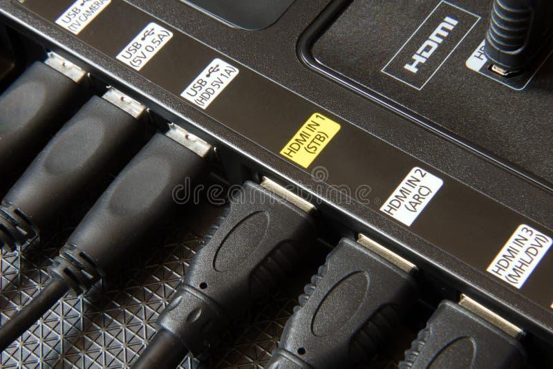 Os cabos de USB e de HDMI obstruíram em entalhes da tevê imagens de stock royalty free