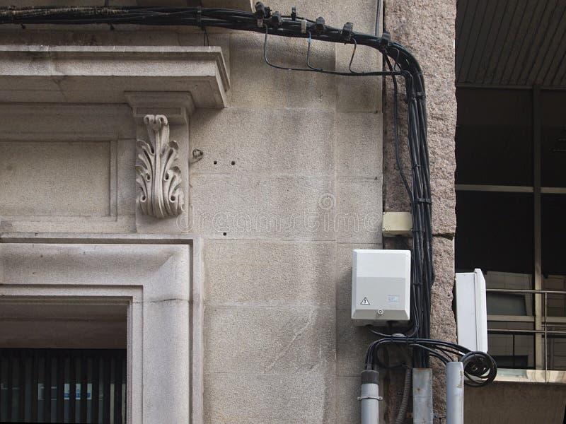 Os cabos desarrumado do telefone ou da eletricidade penduraram em uma parede de pedra foto de stock royalty free